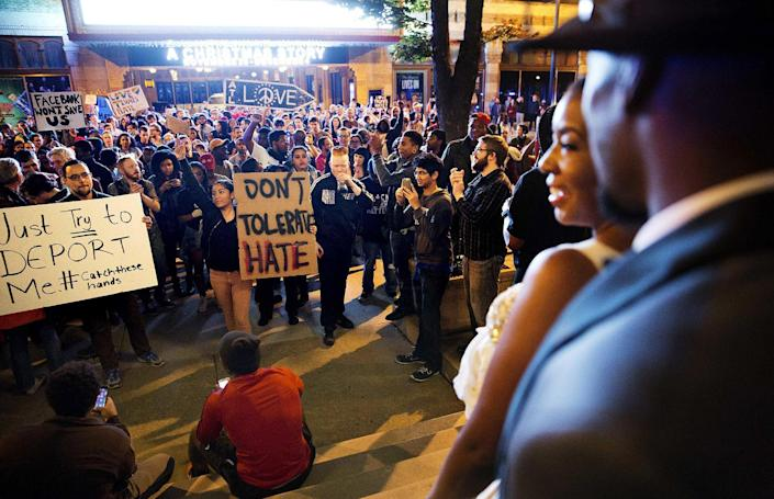 <p>Siedric, right, and Sadio White, step out of a hotel during their wedding party to look on as a protest pauses in the street during a march against the election of President-elect Donald Trump in Atlanta, Friday, Nov. 11, 2016. (AP Photo/David Goldman) </p>