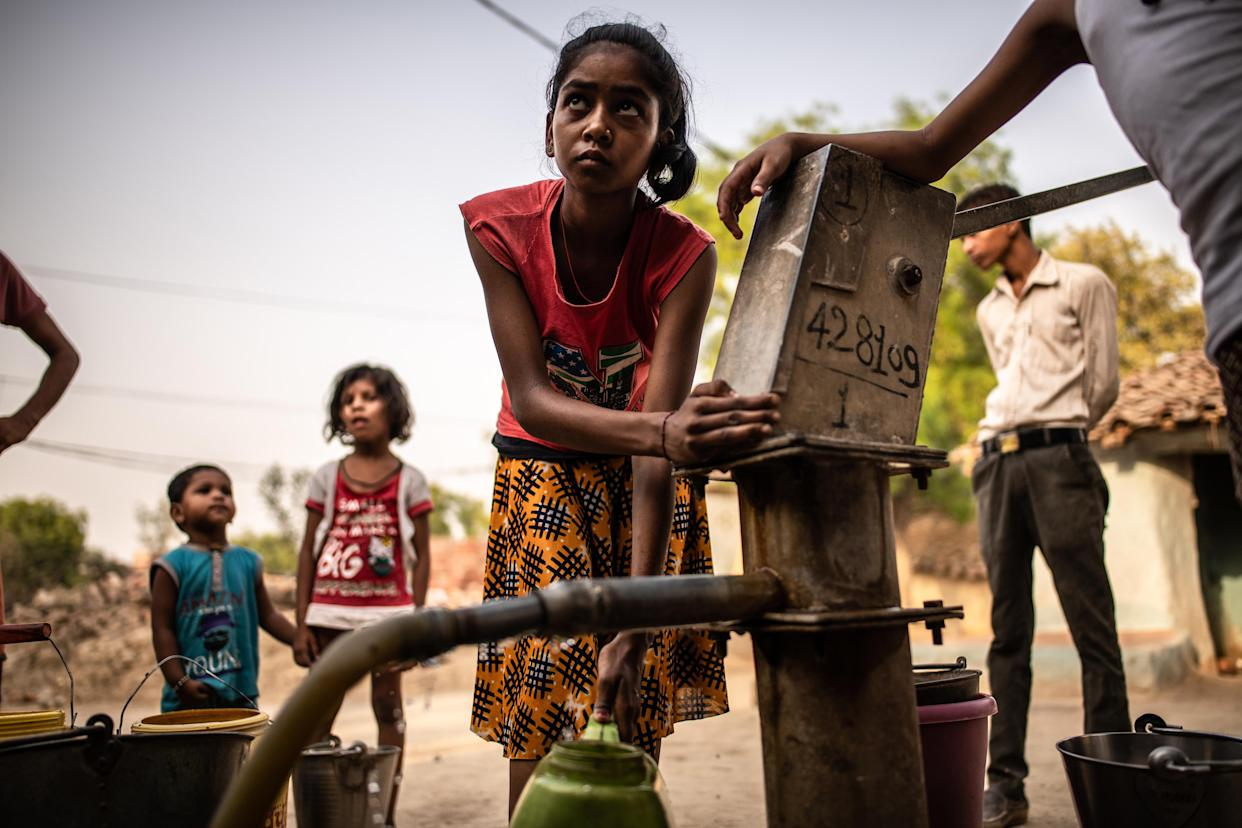 Filling water buckets from a governmental water pump in the drought-ravaged Lamhata village in Uttar Pradesh, India on June 11, 2019. (Bryan Denton/The New York Times)