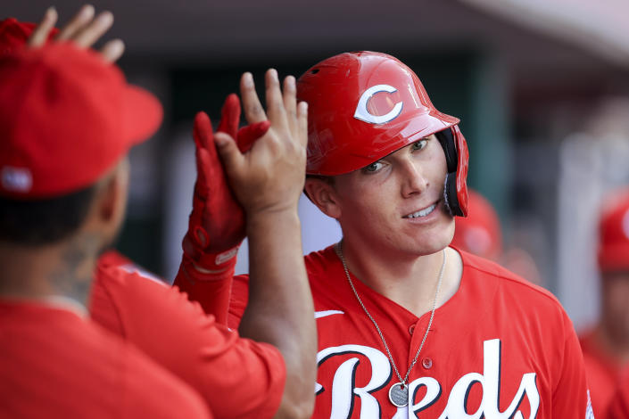 Cincinnati Reds' Tyler Stephenson high-fives teammates ini the dugout after hitting a solo home run during the eighth inning of a baseball game against the Atlanta Braves in Cincinnati, Saturday, June 26, 2021. (AP Photo/Aaron Doster)