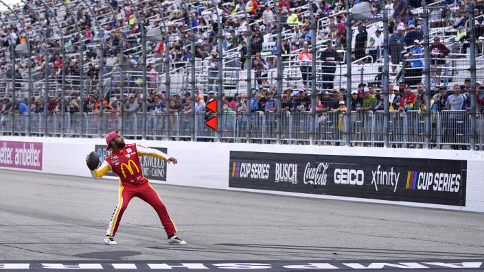 Driver Bubba Wallace throws a football to fans during a rain delay at the NASCAR Cup Series auto race Sunday, July 18, 2021, in Loudon, N.H. (AP Photo/Charles Krupa)