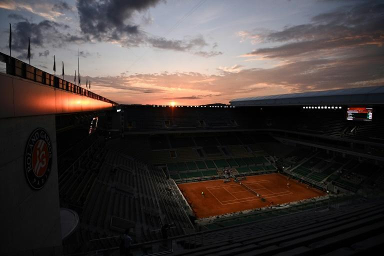 All alone: Rafael Nadal and Richard Gasquet's second-round match was played in front of empty stands as night fell in Paris