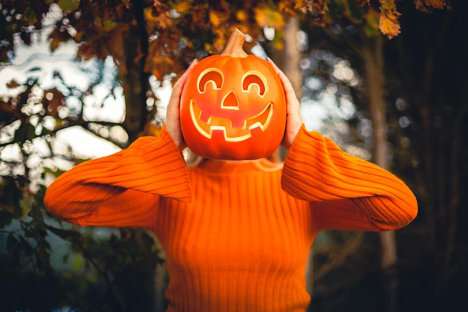 Happy young woman who is in orange jumper, holding a halloween pumpkin against her face at outside