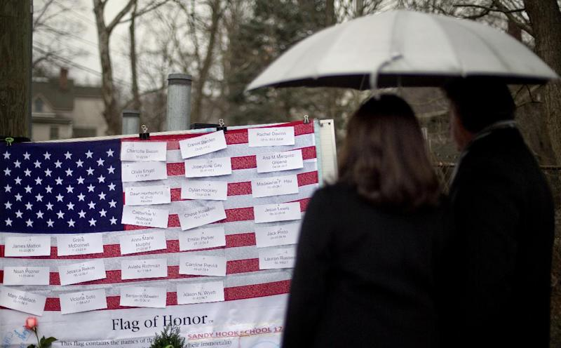 Mourners looks at the names on a U.S. flag of the Sandy Hook Elementary School shooting victims at a sidewalk memorial, Sunday, Dec. 16, 2012, in Newtown, Conn.A gunman walked into Sandy Hook Elementary School in Newtown Friday and opened fire, killing 26 people, including 20 children.  (AP Photo/David Goldman)