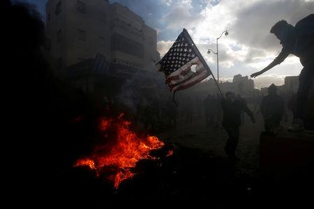 A Palestinian protester prepares to burn a U.S. flag during clashes with Israeli troops at a protest against U.S. President Donald Trump's decision to recognize Jerusalem as the capital of Israel, near the Jewish settlement of Beit El, near the West Bank city of Ramallah December 7, 2017. REUTERS/Mohamad Torokman