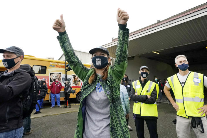 """Liz Baker, CEO of Greater Good Charities, raisers her arms as she watches the landing of a """"Paws Across the Pacific"""" pet rescue flight Thursday, Oct. 29, 2020, in Seattle. Volunteer organizations flew more than 600 dogs and cats from shelters across Hawaii to the U.S. mainland, calling it the largest pet rescue ever. The animals are being taken from overcrowded facilities in the islands to shelters in Washington state, Oregon, Idaho, and Montana. (AP Photo/Elaine Thompson)"""
