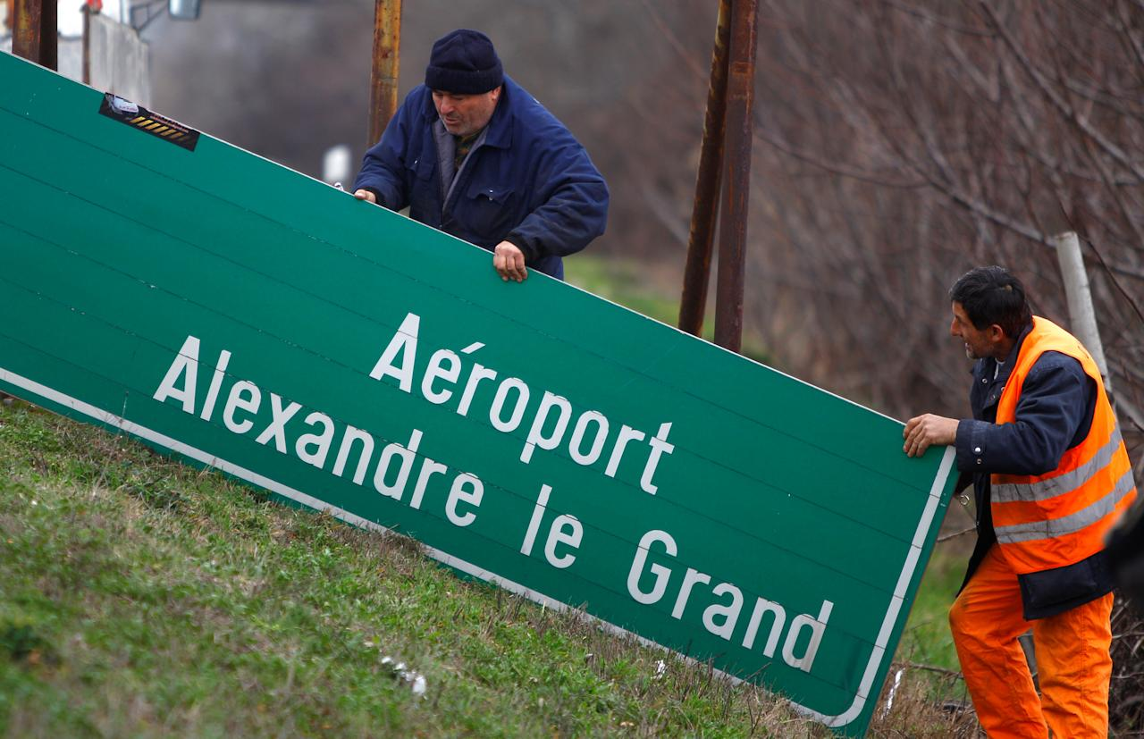 Workers dismantle a road sign with the name 'Alexander the Great Airport' in Skopje, Macedonia February 24, 2018. REUTERS/Ognen Teofilovski?