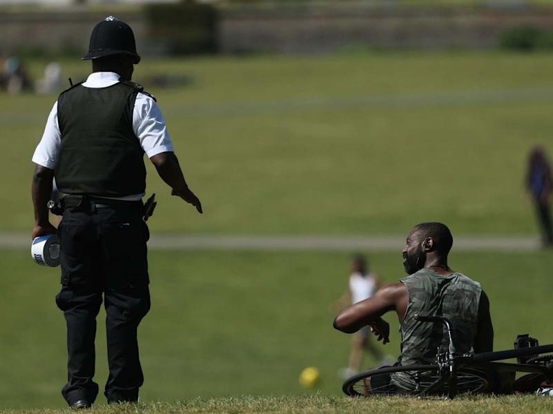 A police officer moves sunbathers in Greenwich Park, London, on 9 May: PA