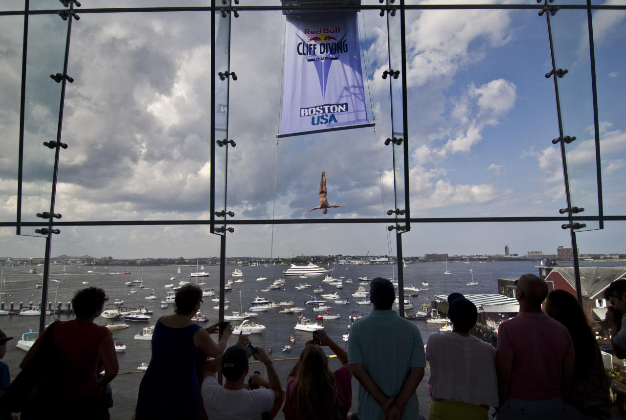 """HANDOUT RESTRICTED TO EDITORIAL USE AND EDITORIAL SALES - MANDATORY CREDIT """"AFP PHOTO / RED BULL / Romina AMATO""""  This handout photo received by Red Bull and taken on August 20, 2011 shows Cyrille Oumedjkane of France as he dives from the 26.5 metre platform on the Institute of Contemporary Art building during the sixth stop of the Red Bull Cliff Diving World Series at Fan Pier in Boston. Gary Hunt of Great Britain has an almost unassailable lead with one stop in the series remaining in Yalta, Ukraine, in two weeks.  AFP PHOTO / HO / RED BULL / Romina AMATO (Photo credit should read Romina AMATO/AFP/Getty Images)"""