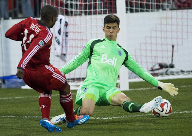 Toronto FC forward Jermain Defoe, left, score past Vancouver Whitecaps goal keeper Marco Carducci, right, during first half semi-final Amway Canadian Championship soccer action in Toronto on Wednesday, May 7, 2014. (AP Photo/The Canadian Press, Nathan Denette)