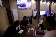 Iraqis gather at a cafe in Baghdad's Karrada neighbourhood on the day of the US presidential election, with news coverage of that poll airing on television