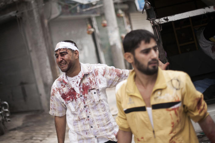 A Syrian man, wounded by Syrian Army shelling, cries while the bodies of his relatives lie on the street near Dar El Shifa hospital in Aleppo, Syria, Thursday, Oct. 11, 2012. (AP Photo/ Manu Brabo)