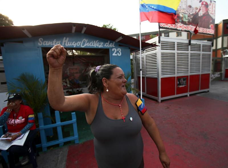 "Elizabeth Torres, supporter of late Venezuela's President Hugo Chavez, clenches her fist while guarding a people's shrine built in his honor at the ""23 de Enero"" or ""23rd of January"" slum in Caracas, Venezuela, Wednesday, April 3, 2013. The shrine, named ""Saint Hugo Chavez del 23"", has been visited by tens of thousands of Venezuelans to pay homage to a president for some, a saint for others. (AP Photo/Fernando Llano)"