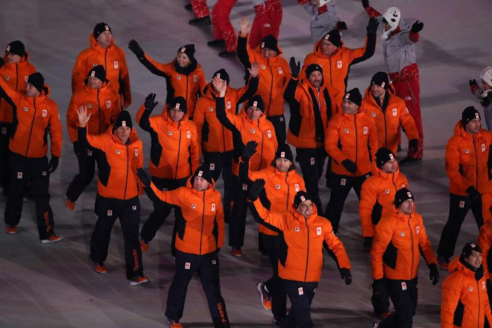 <p>Team Netherlands walks in the Parade of Athletes wearing orange winter jackets anad black pants designed by Fila during the opening ceremony of the 2018 PyeongChang Games. (Photo: Sean M. Haffey/Getty Images) </p>