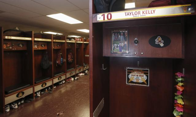 Arizona State quarterback Taylor Kelly has a variety of photos of his family at his locker in the Arizona State football team locker room Monday, Aug. 11, 2014, in Tempe, Ariz. Each player and coach on Arizona State's team has a photo above their locker of someone who has inspired them. There are mothers, fathers, siblings, grandparents, a few coaches. Coach Todd Graham had them all do it so they can remember it's not just their teammates they're playing for. (AP Photo/Ross D. Franklin)