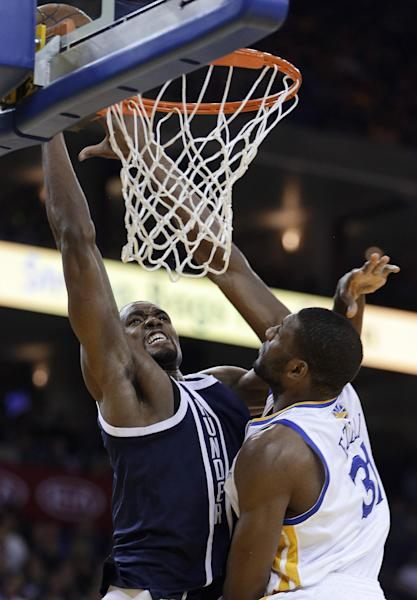 Oklahoma Thunder forward Serge Ibaka, left, lays up a shot against Golden State Warriors' Festus Ezeli during the first half of an NBA basketball game Thursday, April 11, 2013, in Oakland, Calif. (AP Photo/Ben Margot)