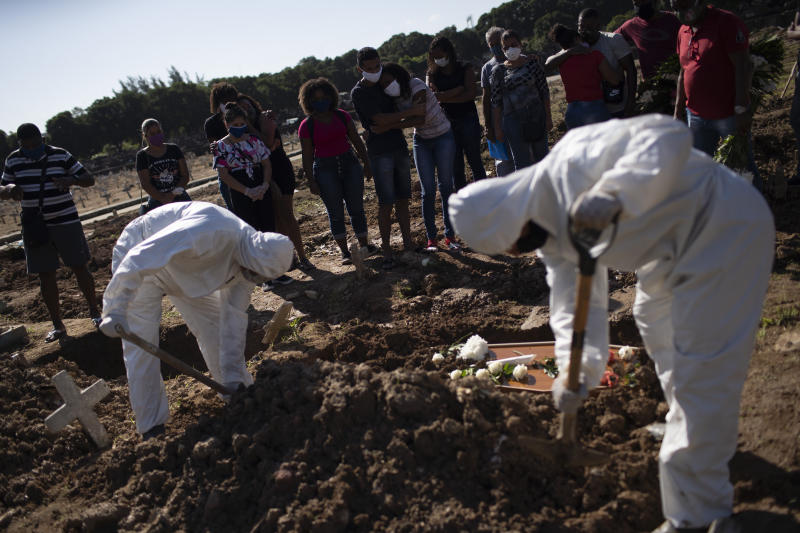 Relatives watch cemetery workers shovel dirt over the casket of 22-year-old COVID-19 victim Amanda da Silva at the Caju cemetery in Rio de Janeiro, Brazil, Wednesday, May 20, 2020. (AP Photo/Silvia Izquierdo)