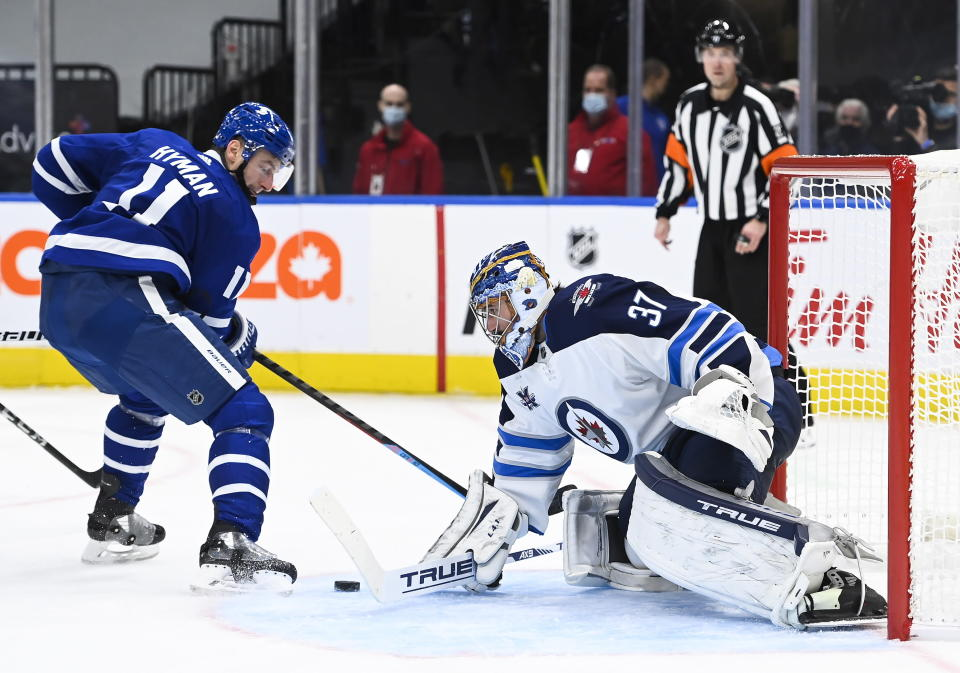 Winnipeg Jets goaltender Connor Hellebuyck (37) makes a save against Toronto Maple Leafs left wing Zach Hyman (11) during third period NHL hockey action in Toronto on Monday, Jan. 18, 2021. (Nathan Denette/The Canadian Press via AP)