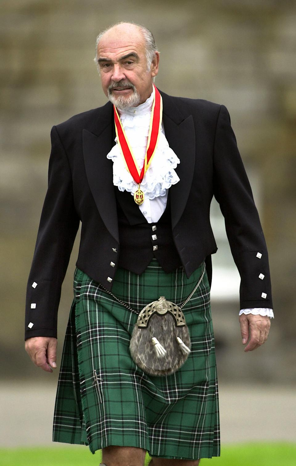 Connery wears full Highland dress and his medal after he was formally knighted by the queen in July 2000. (Photo: David Cheskin/PA Archive)