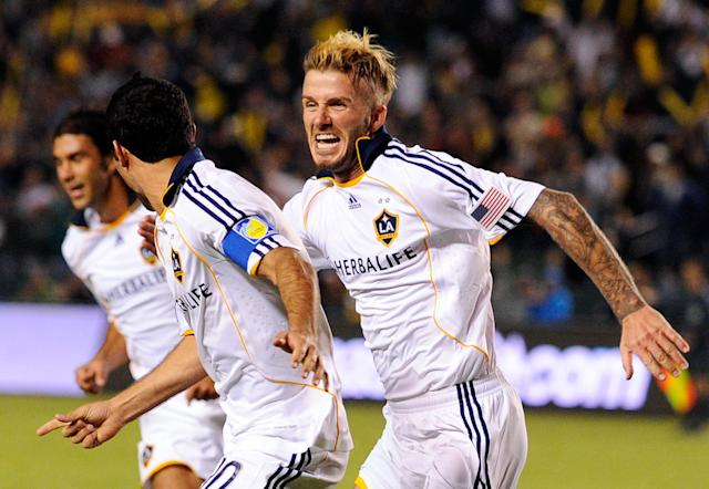 CARSON, CA - NOVEMBER 13: David Beckham #23 (R) of the Los Angeles Galaxy chases teammate Landon Donovan #10 to celebrate after Donovan's goal on a penalty kick against Houston Dynamo during the MLS Western Conference Championship soccer match at The Home Depot Center on November 13, 2009 in Carson, California. (Photo by Kevork Djansezian/Getty Images)