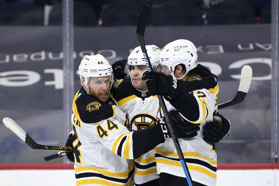 Boston Bruins' Jake DeBrusk, center, celebrates his goal with Steven Kampfer (44) and Craig Smith during the second period of an NHL hockey game against the Philadelphia Flyers, Saturday, April 10, 2021, in Philadelphia. (AP Photo/Derik Hamilton)