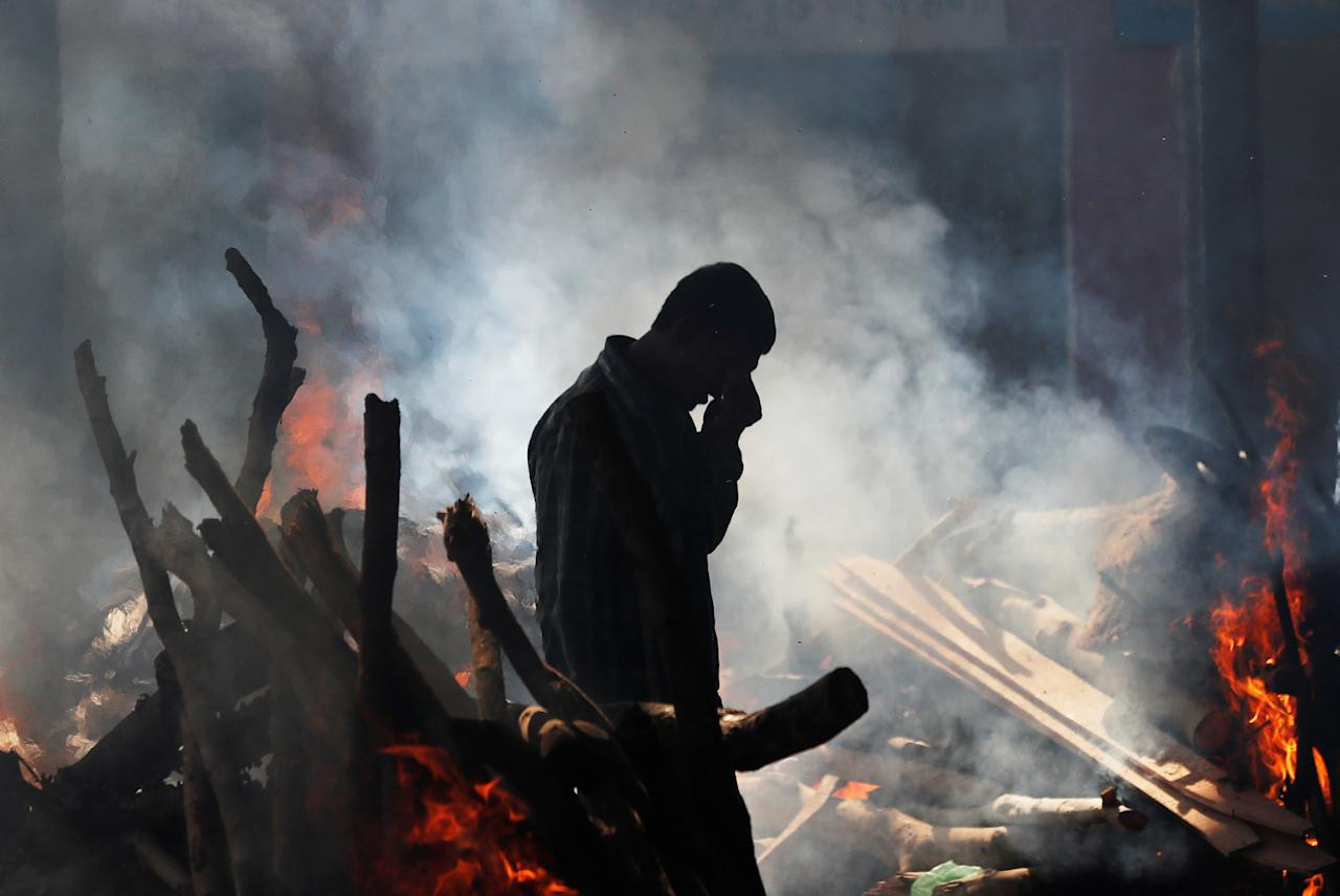 <p>A man cries as he stands next to the burning pyre of a family member who died after a commuter train traveling at high speed ran through a crowd of people on the rail tracks on Friday, at a cremation ground in Amritsar, India, Oct. 20, 2018. (Photo: Adnan Abidi/Reuters) </p>