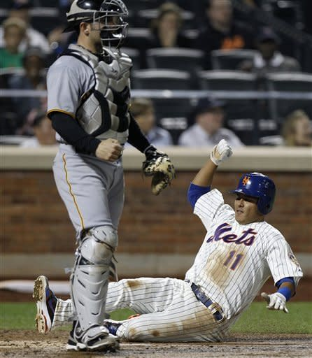 New York Mets shortstop Ruben Tejada scores in front of Pittsburgh Pirates catcher Michael McKenry (55) on Daniel Murphy's third-inning single in their baseball game at Citi Field in New York , Wednesday, Sept. 26, 2012. (AP Photo/Kathy Willens)