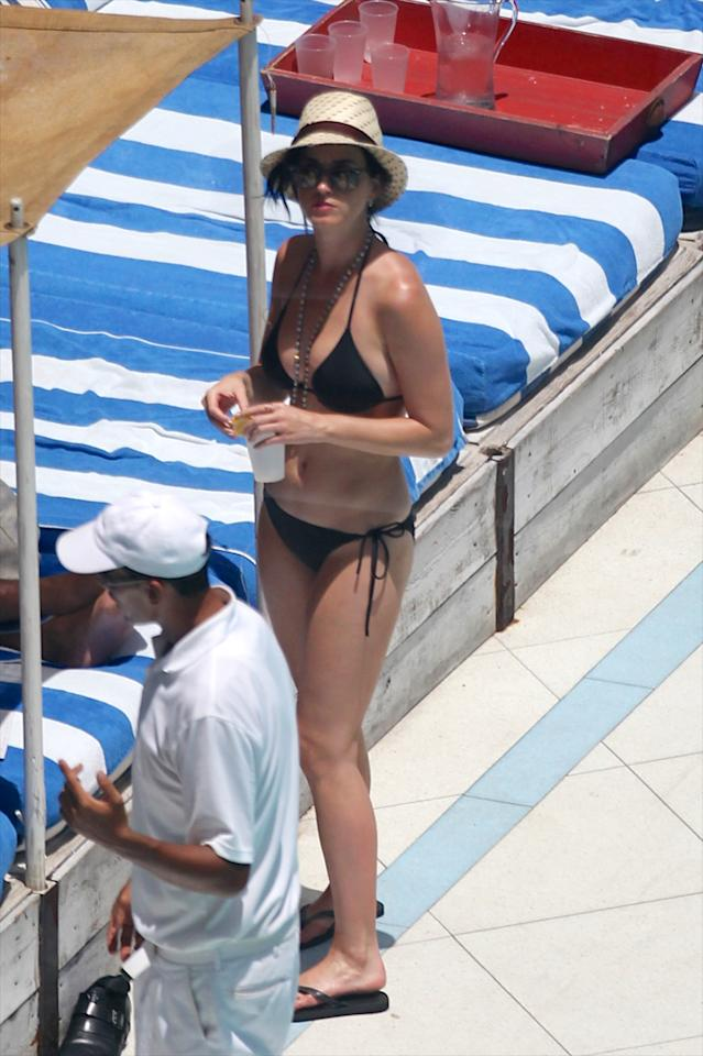 The 27-year-old flaunted her killer curves in a classic black bikini, fedora, and Ray Ban sunglasses as she lounged poolside. (7/27/2012)