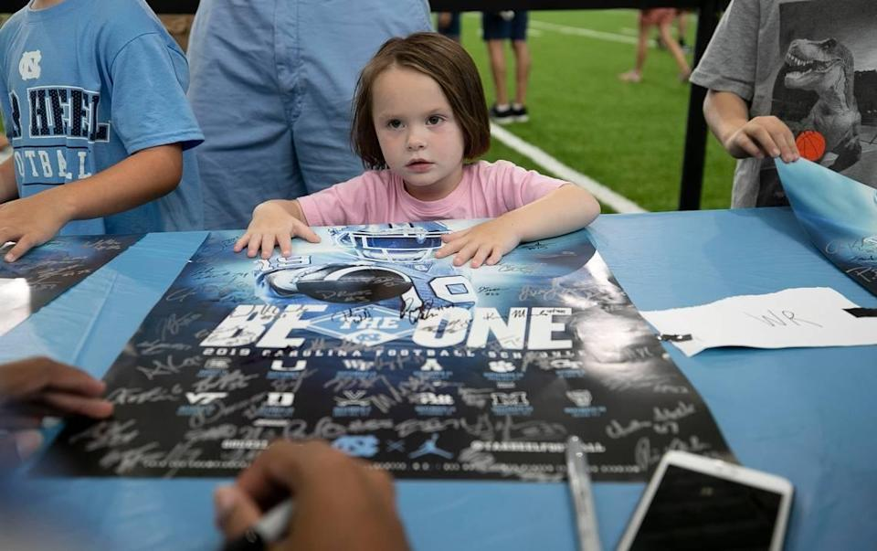 Three-year-old Shea Caudill of Mebane, N.C. gets an autograph from North Carolina receiver Welton Spottsville (17) during the annual Meet The Heels event on Saturday, August 3, 2019 at the Football Practice Complex in Chapel Hill, N.C.