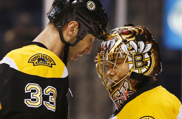 Boston Bruins goalie Tuukka Rask of Finland is congratulated by defenseman Zdeno Chara (33) of Slovakia after their 2-1 win over the Phoenix Coyotes in an NHL hockey game in Boston Thursday, March 13, 2014. (AP Photo/Winslow Townson)