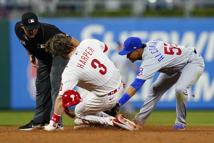 Philadelphia Phillies' Bryce Harper, center, slides into second for an RBI-double past the tag from Chicago Cubs shortstop Sergio Alcantara, right, during the sixth inning of a baseball game, Tuesday, Sept. 14, 2021, in Philadelphia. (AP Photo/Matt Slocum)