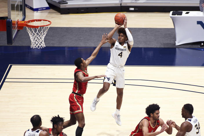 West Virginia guard Miles McBride (4) shoots while defended by Northeastern guard Shaquille Walters (24) during the first half of an NCAA college basketball game Tuesday, Dec. 29, 2020, in Morgantown, W.Va. (AP Photo/Kathleen Batten)