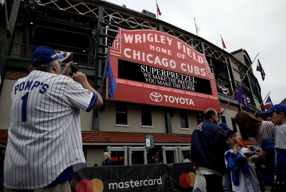 Chicago Cubs fans wait outside Wrigley Field before the National League wild-card playoff baseball game between the Colorado Rockies and the Chicago Cubs, Tuesday, Oct. 2, 2018, in Chicago. (AP Photo/Nam Y. Huh)