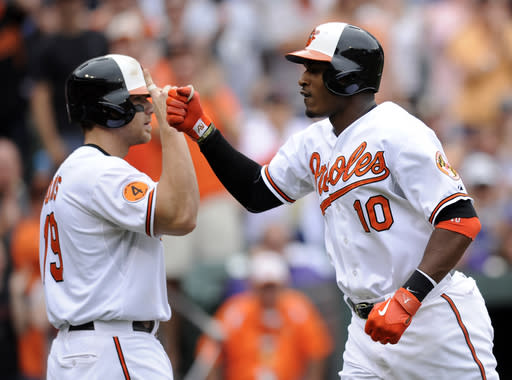 Baltimore Orioles' Adam Jones (10) celebrates his two-run home run with teammate Chris Davis, left, against the Colorado Rockies during the third inning of a baseball game on Sunday, Aug. 18, 2013, in Baltimore. (AP Photo/Nick Wass)