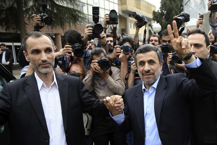 Former Iranian President Mahmoud Ahmadinejad, right, and his close ally Hamid Baghaei flash the victory sign as they arrive at the Interior Ministry to register their candidacy for the upcoming presidential elections, in Tehran, Iran, Wednesday, April 12, 2017. Ahmadinejad on Wednesday unexpectedly filed to run in the country's May presidential election, contradicting a recommendation from the supreme leader to stay out of the race. (AP Photo/Ebrahim Noroozi)