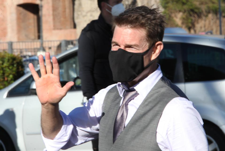 Tom Cruise wears a face mask to prevent the spread of COVID-19 as he waves to fans during a break from shooting the film Mission Impossible 7- Libra, along Rome's Fori Imperiali avenue