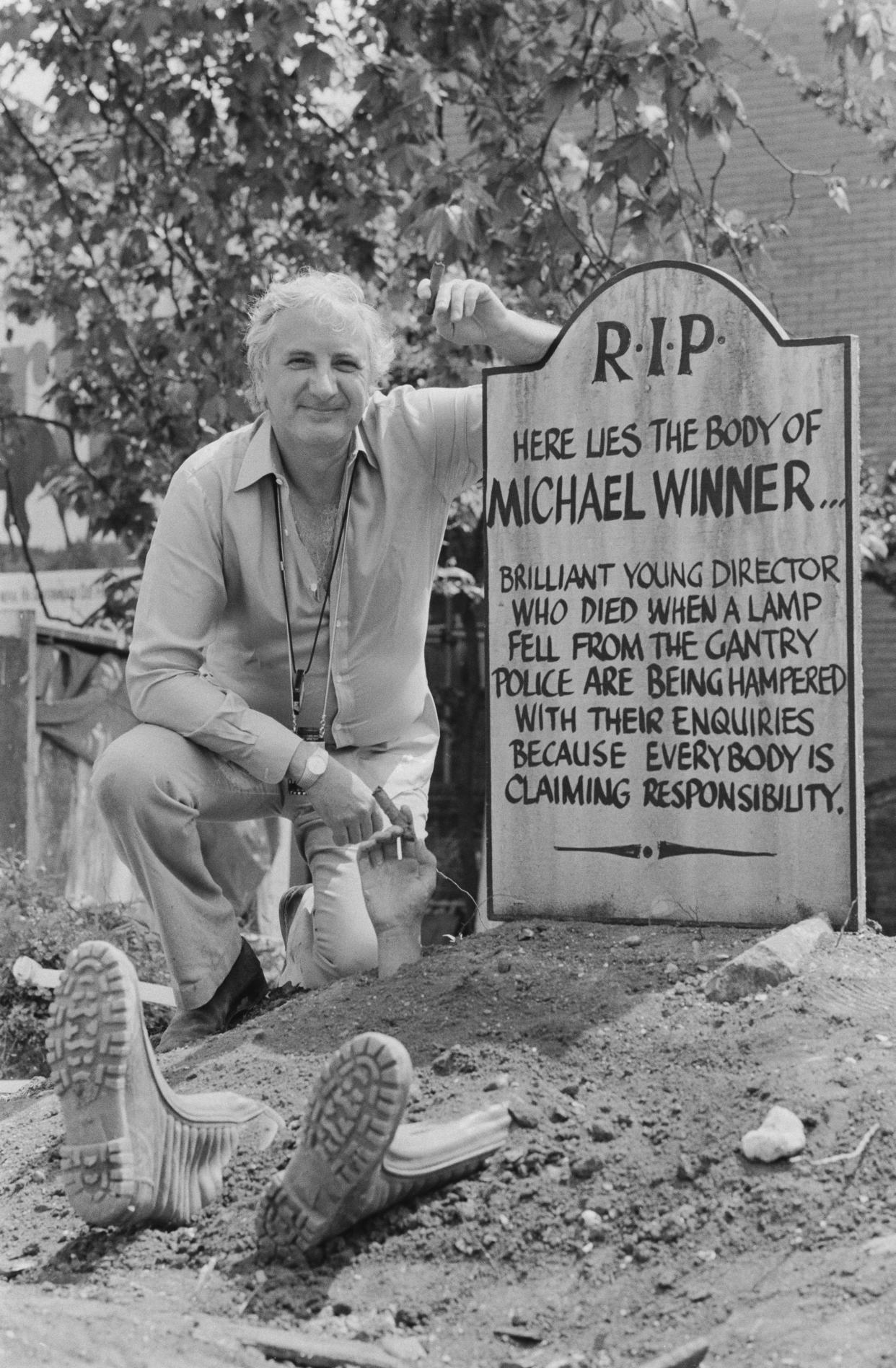 English film director and producer Michael Winner standing next to a fake tombstone which reads