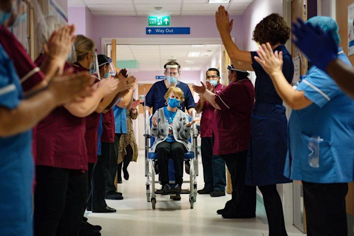 Margaret Keenan, 90, is applauded by staff as she returns to her ward after becoming the first person in the United Kingdom to receive the Pfizer/BioNtech COVID-19 vaccine at University Hospital on December 8, 2020 in Coventry, United Kingdom.