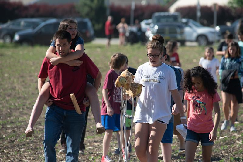 Evacuated students and staff march to buses to be carried offsite outside Noblesville West Middle School.