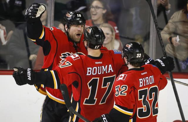 Calgary Flames' Brian McGrattan, left, celebrates his goal with teammates TJ Brodie, center, and Paul Byron during the second period of an NHL hockey game, Thursday, Dec. 12, 2013 in Calgary, Alberta. (AP Photo/The Canadian Press, Jeff McIntosh)