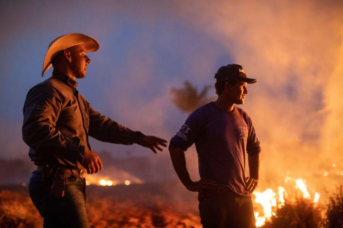 A laborer with a friend looks at a fire that spread to the farm he works on next to a highway in Nova Santa Helena municipality in northern Mato Grosso State, south in the Amazon basin in Brazil, on Aug. 23, 2019. (Photo: Joao Laet/AFP/Getty Images)