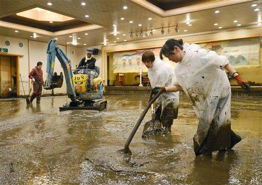 Workers shovel muddy water out of a banquet room of a hotel in Aso, Kumamoto Prefecture, Japan, Saturday, July 14, 2012. Heavy rain triggered flash floods and mudslides in southern Japan this week, killing nearly two dozens of people. (AP Photo/Kyodo News)