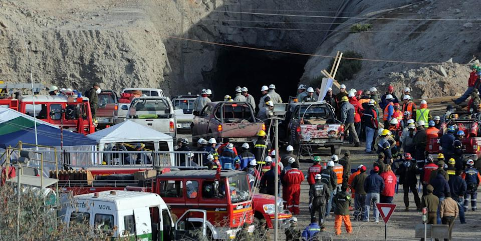 Rescuers, miners and relatives gather at the entrance to the San Esteban gold and copper mine near the city of Copiapo, in the arid Atacama desert, 800 kilometers (480 miles) north of Santiago, on August 7, 2010. Dozens of rescue workers scrambled Friday to locate 34 miners trapped inside a copper and gold mine in northern Chile after a cave-in. It was not immediately clear if there were casualties from the accident.  AFP PHOTO/Martin Bernetti (Photo credit should read MARTIN BERNETTI/AFP via Getty Images)