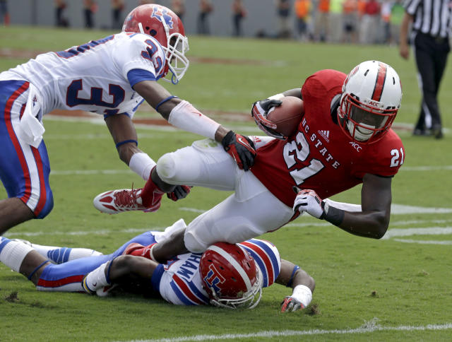 North Carolina State's Matt Dayes (21) is tackled by Louisiana Tech's Thomas McDonald (33) and Bryson Abraham, bottom, during the first half of an NCAA college football game in Raleigh, N.C., Saturday, Aug. 31, 2013. (AP Photo/Gerry Broome)