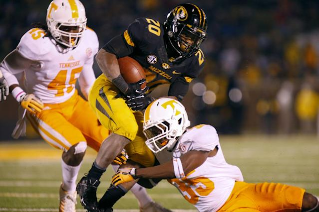 COLUMBIA, MO - NOVEMBER 2: Jaron Toney #35 of the Tennessee Volunteers wraps up the legs of Henry Josey #20 of the Missouri Tigers late in the third quarter on November 2, 2013 at Faurot Field/Memorial Stadium in Columbia, Missouri. (Photo by Kyle Rivas/Getty Images)