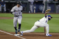 Colorado Rockies' Trevor Story, left, looks at Seattle Mariners first baseman Evan White after grounding out in the third inning of a baseball game Sunday, Aug. 9, 2020, in Seattle. (AP Photo/Elaine Thompson)