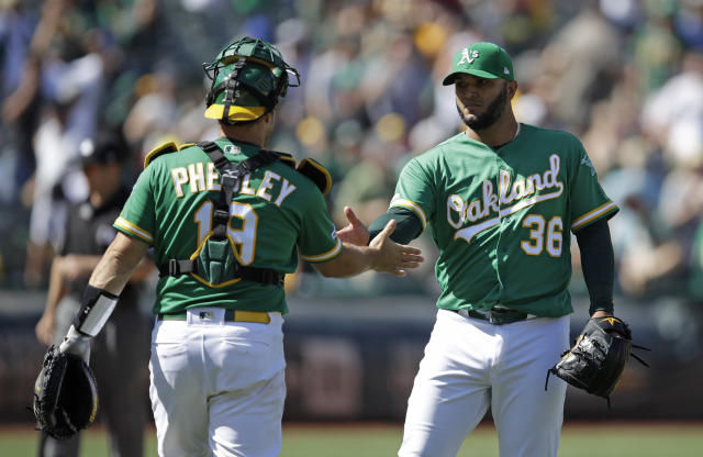Oakland Athletics pitcher Yusmeiro Petit, right, celebrates the team's 8-4 win over the Houston Astros with catcher Josh Phegley at the end of a baseball game Saturday, Aug. 17, 2019, in Oakland, Calif. (AP Photo/Ben Margot)