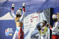 Switzerland's Corinne Suter celebrates on the podium after winning the gold medal in the women's downhill, at the alpine ski World Championships in Cortina d'Ampezzo, Italy, Saturday, Feb. 13, 2021. (AP Photo/Marco Tacca)