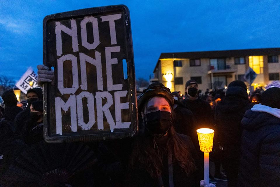TOPSHOT - Demonstrators hold candles and signs as they protest peacefully ahead of the 10pm curfew, in front of the Brooklyn Central Police Station in Brooklyn Center, Minnesota on April 15, 2021. - Kim Potter, the policewoman who shot dead Daunte Wright in a Minneapolis suburb after appearing to mistake her gun for her Taser, was arrested on Wednesday on manslaughter charges. Minneapolis has been roiled by nightly violent protests after Potter's shooting of Wright in his car on Sunday. (Photo by Kerem Yucel / AFP) (Photo by KEREM YUCEL/AFP via Getty Images)