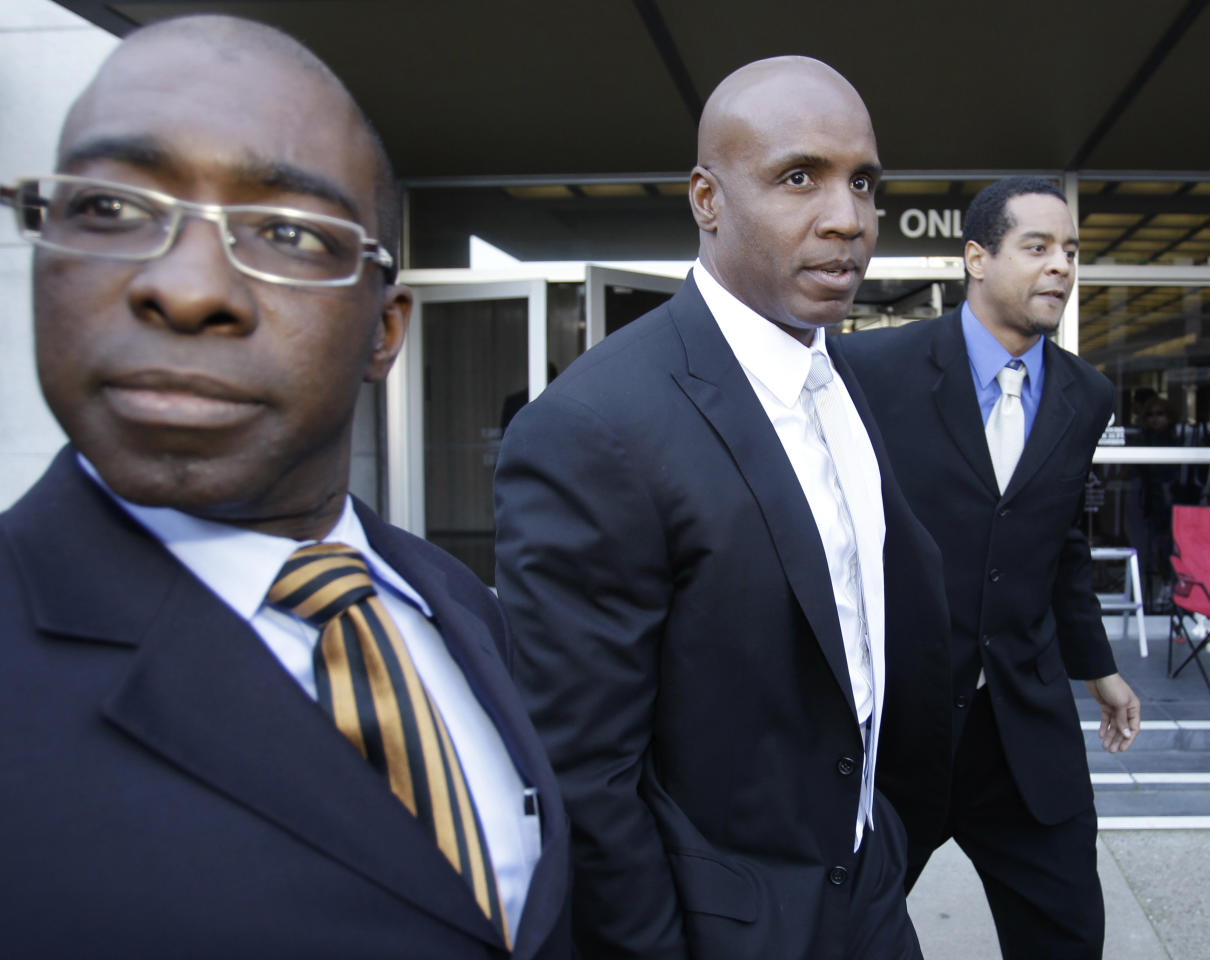 Former baseball player Barry Bonds, center, is surrounded by unidentified supporters as he leaves a federal courthouse for his perjury trial, Wednesday, April 6, 2011, in San Francisco.