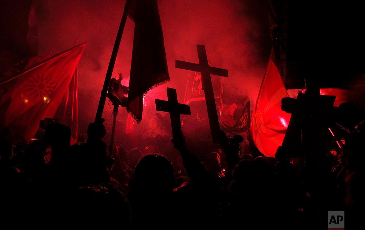 <p>Protestors carry crosses and light torches during a protest against the change of the country's constitutional name, in front of the Parliament building in Skopje, Macedonia. Several thousand protestors have gathered in front of Macedonia's parliament to demand that the government call off talks with neighbour Greece on a decades-long name dispute. (AP Photo/Boris Grdanoski) </p>